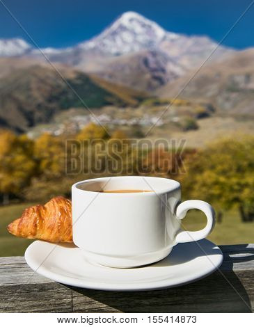 Cup of coffee and Croissants  among beautiful nature of Georgia , Europe.
