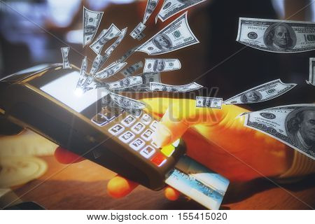 Hand holding POS terminal with credit card and abstract dollar bills flying out of screen. Money concept