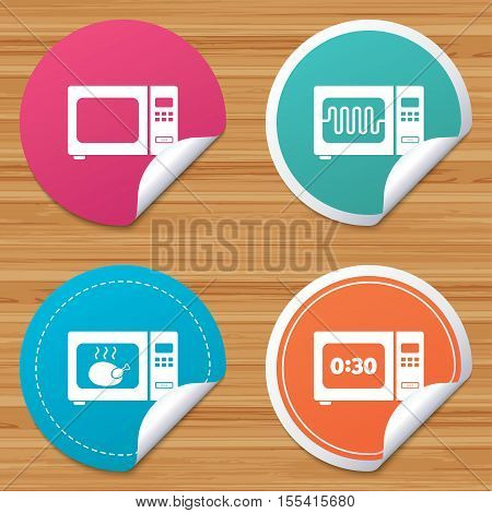 Round stickers or website banners. Microwave oven icons. Cook in electric stove symbols. Grill chicken with timer signs. Circle badges with bended corner. Vector