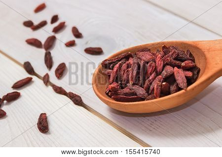 Goji berries in a wooden spoon on a white background. Healthy eating.