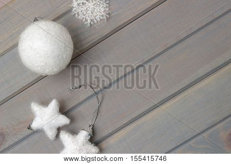 Christmas ornaments in white on a light gray wooden background. New Year's accessories. View from above. Space for text