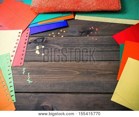 Craft making. Making a greeting card. Colored paper applique handmade. Dark wood background.
