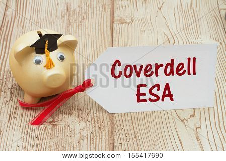 Your Coverdell education savings account A golden piggy bank and grad cap on a desk with a gift tag with text Coverdell ESA