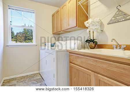 Bright Interior Of Laundry Room With Cabinets And White Appliances