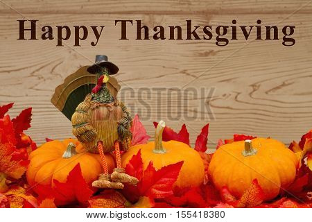 Happy Thanksgiving greeting Some fall leaves pumpkins and a turkey on weathered wood with text Happy Thanksgiving