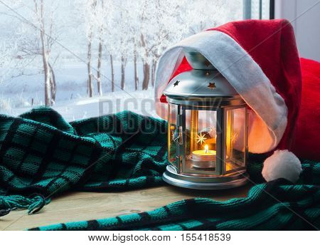 Lantern with candle and Christmas Santa hat on the windowsill and winter forest outdoors-Christmas and New Year winter background. Christmas concept. Festive Christmas winter still life. Christmas in home-holiday Christmas background