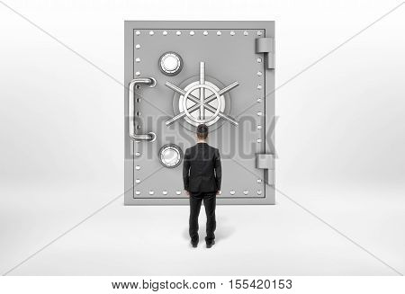 A businessman standing back to us looking at the giant safe door, all isolated on the grey background. Business and banking. Success and wealth. Money problems.