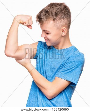 Thin caucasian teen boy wearing blue t-shirt showing off his biceps. Happy teenager showing his hand biceps muscles strength, isolated on white background. Sports theme and childhood concept - child in studio.