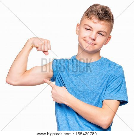 Thin caucasian teen boy wearing blue t-shirt showing off his biceps. Sad teenager showing his hand biceps muscles strength, isolated on white background. Sports theme and childhood concept - child in studio.