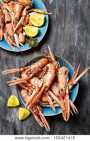 Fresh scampi served with lemon on old wooden table