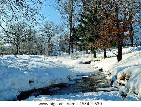 Winter rural landscape in sunny weather- winter view of rural houses with stream and winter snowdrifts on the foreground. Sunny view of picturesque winter nature. Rural winter landscape under sunshine