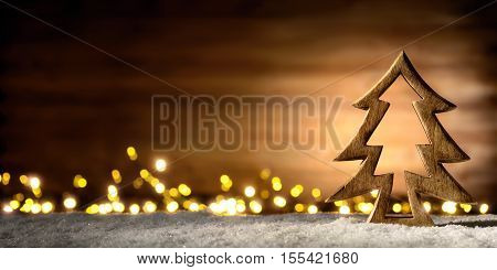 Cozy Christmas arrangement with beautiful wooden ornaments on snow in the warm candlelight of a nice lantern low-key studio shot