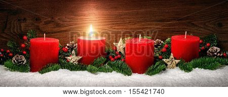 Low-key studio shot of elegant advent decoration with fir branches on snow and one burning red candle dark wood background