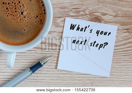 Hand writing the text Whats Your Next Step. Morning coffee at wooden table background.