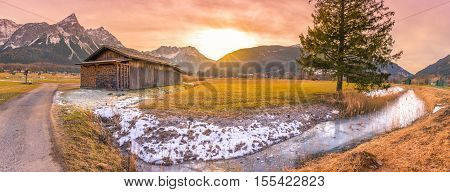 Winter sunset in the Austrian Alps - Idyllic winter scenery in a small Austrian village with a wooden barn a frozen river and the Alps mountains at dusk.
