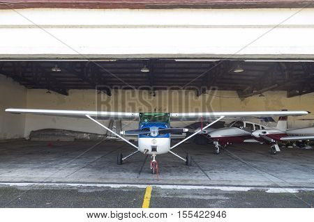 Single engine private lightweight aircraft in hangar.