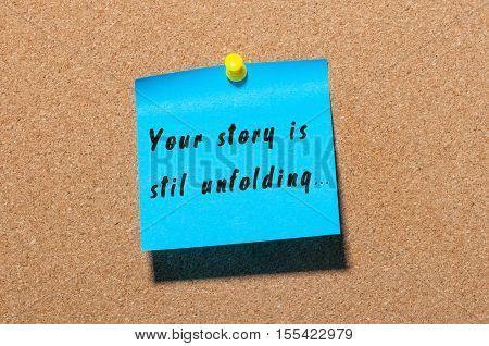 Your Story Is Still Unfolding motivation inscription written on blue sticker pinned at cork notice background.
