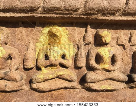 Stone carved Buddha with gold leaf. Stone carved relief on ancient hindu temple. Traditional indian art. Buddhist decoration. India place of interest. Yoga lotus pose of meditating people