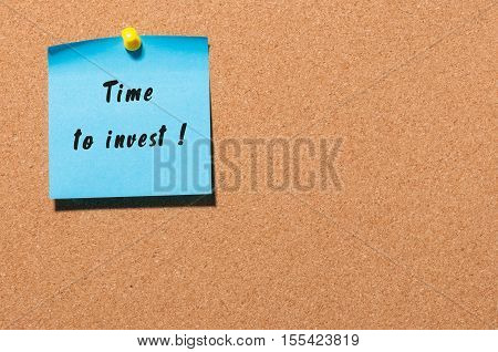 Time to Invest inscription written on blue sticker pinned at cork notice board with empty space.