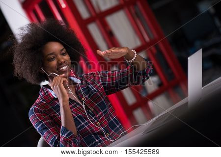 black woman in modern office at her workplace speeking on phone over earphones and working on laptop computer