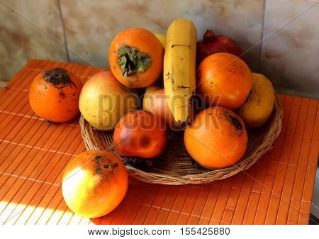 A still life of autumn fruit of blood oranges,apples,bananas and pomegranates on a wattled plate