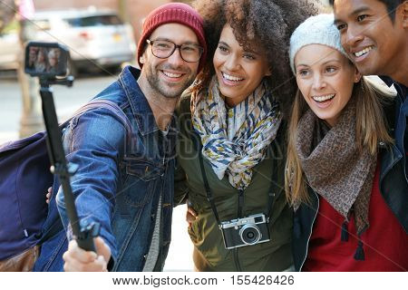 Group of friends on vacation taking selfie picture with camera