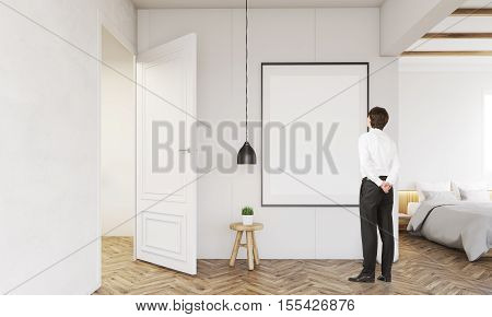 Rear view of businessman standing in his bedroom and looking at blank framed poster on the wall. Concept of home decoration. Mock up. 3d rendering