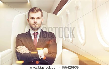 Portrait of businessman sitting in business class of a plane with his arms crossed. Concept of success and luxury. Toned image. 3d rendering.
