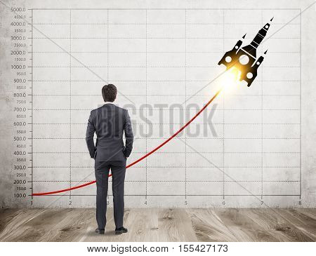 Rear view of businessman with brown hair looking at concrete wall with graph and a rocket sketch on it. Concept of new project