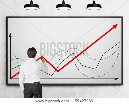 Rear view of businessman in white shirt drawing a graph on whiteboard. Concept of statistician's work