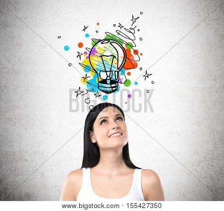 Smiling woman in white tank top standing under colorful light bulb sketch drawn on concrete wall above her head. Concept of creative approach to problem solving