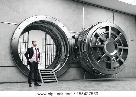 Confident businessman is standing near wide open vault door. Concept of money saving. 3d rendering.