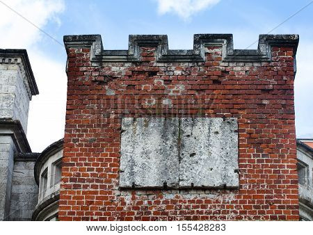 Redbrick tower in the old wall masonry. Aged bricks, white seam