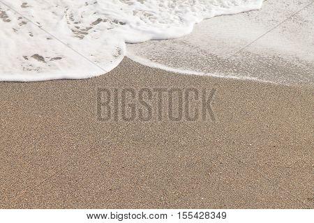 oncoming wave foam on a sandy beach