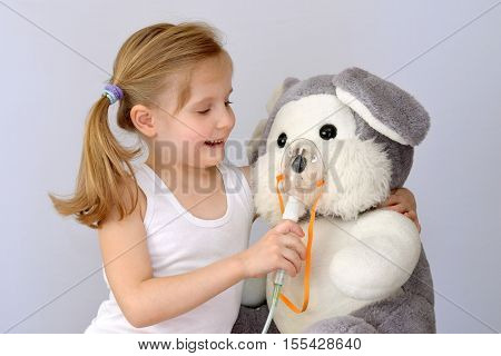 Child (girl) with an inhaler (nebulizer) makes the  procedure a soft toy.