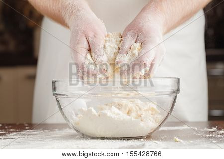 Hands Of Man Preparing Mound Of Bread Dough On Clear Black Table Coated With Flour To Prevent Sticki