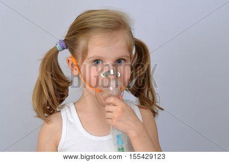 Child, kid (little girl) with inhaler (nebulizer) makes the procedure.