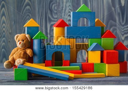 building from wooden colourful childrens blocks with toy bear