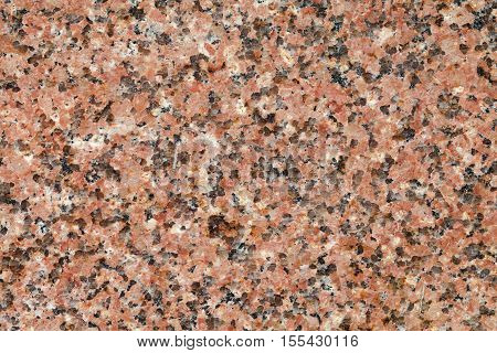 Pink granite tile pattern. Polished surface of granite stone with rosy black hues. macro
