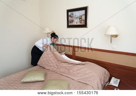 MOSCOW - OCTOBER 31: Supervisor girl dressed in white and black checking cleanliness of bed at room in Izmaylovo hotel on October 31 2016 in Moscow. Izmailovo Hotel is four-building hotel located in Izmaylovo District of Moscow.