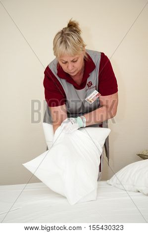 MOSCOW - OCTOBER 31: Maid woman dressed in red and gray putting pillowcase on pillow at room in Izmaylovo hotel on October 31 2016 in Moscow. Izmailovo Hotel is four-building hotel located in Izmaylovo District of Moscow.