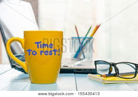 Time to rest concept inscription on yellow morning coffee cup at business office background. Hard working consept.