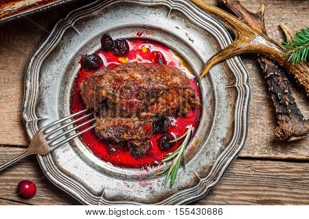 Venison served with cranberry sauce on old wooden table