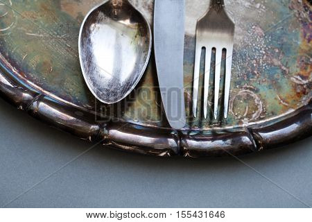 Kitchen tableware set on the vintage silver tray. spoon, knife and fork. gray paper background.