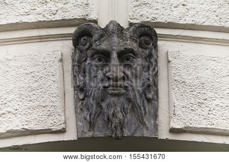 Sculpture of Lucifer face with horns. Demon evil mascarone architecture element building's facade background. Shallow depth of field