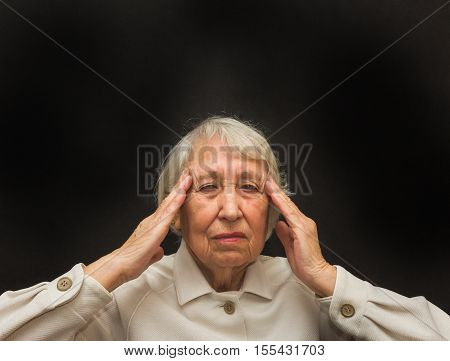 Senior Woman With Head In Hands Looking Weary on black