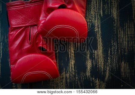Red leather boxing gloves for boxing on a black background horizontal composition