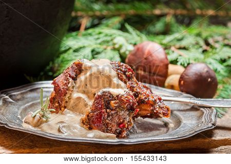 Roasted venison served with mushroom sauce on old wooden table
