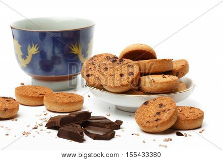 Beautiful blue chinese tea cup with yellow ornament tasty biscuit cookies and dark chocolate pieces and chips lie isolated on white background. Shallow DOF. Focus on cookies in saucer.