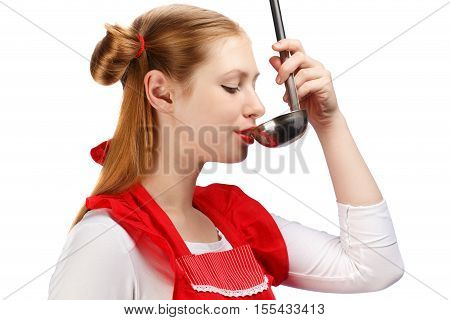 Young beautiful attractive housewife in bright red apron with funny ponytails tasting meal from ladle isolated on white background. Close up.